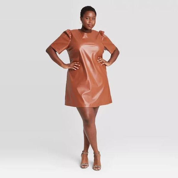 A plus-size model from Target wearing a faux leather mini dress in brown.