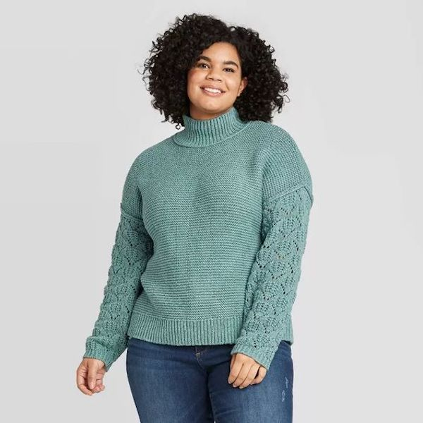 A plus-size model from Target wearing a light blue sweater.