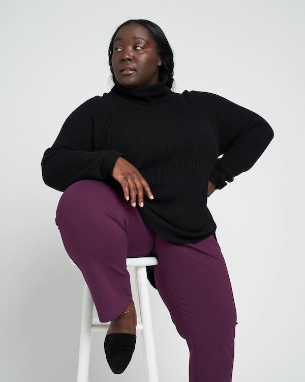 A plus-size model from Universal Standard wearing a black sweater and purple pants.