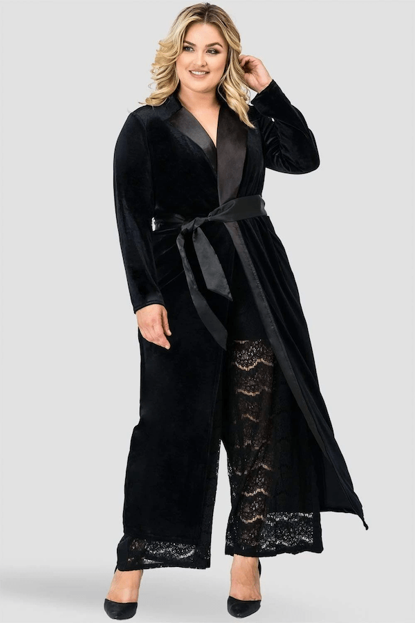 A plus-size model wearing a long black velvet jacket.