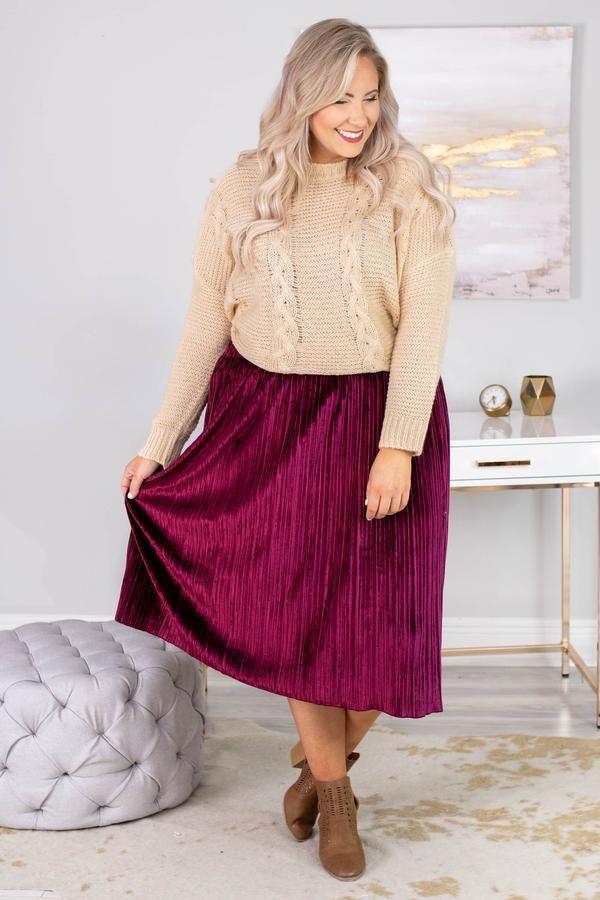 A plus-size model wearing a magenta velvet skirt.