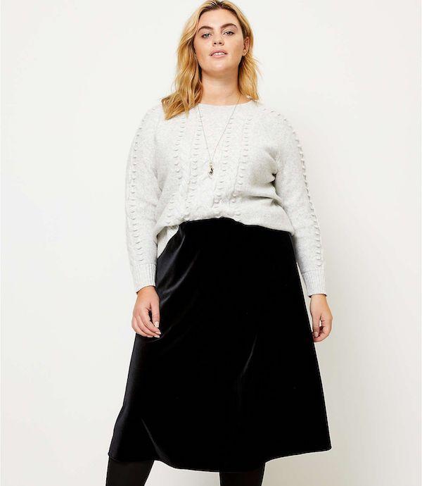 A plus-size model wearing a black velvet skirt.