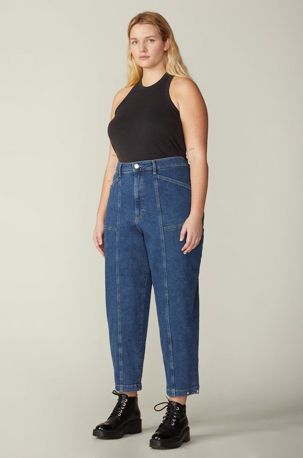 A plus-size model from Warp + Weft wearing pleated jeans.