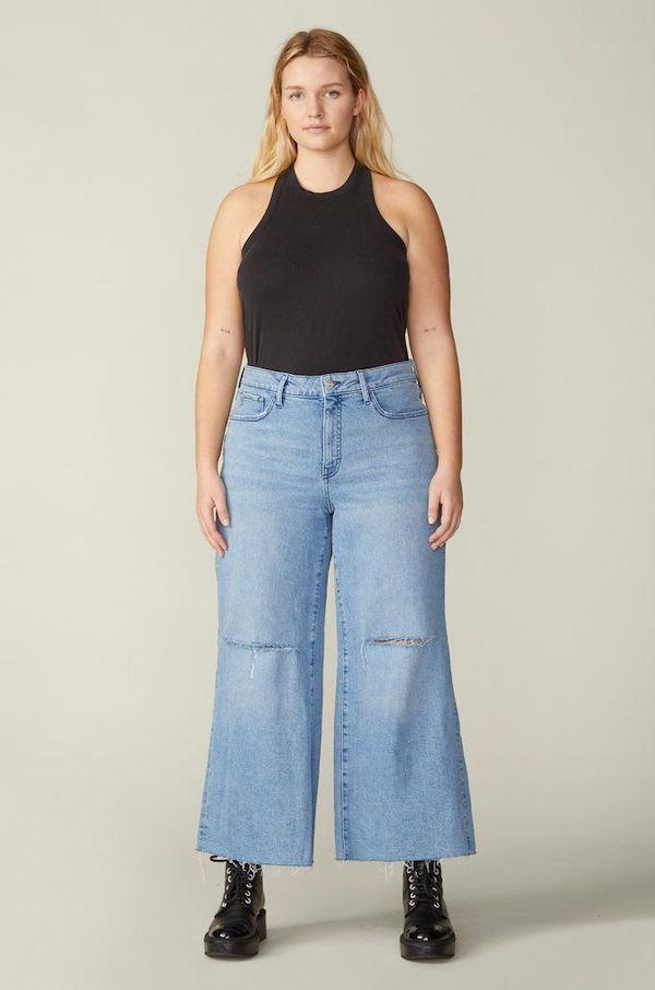 A plus-size model from Warp + Weft wearing light-wash wide-leg jeans.