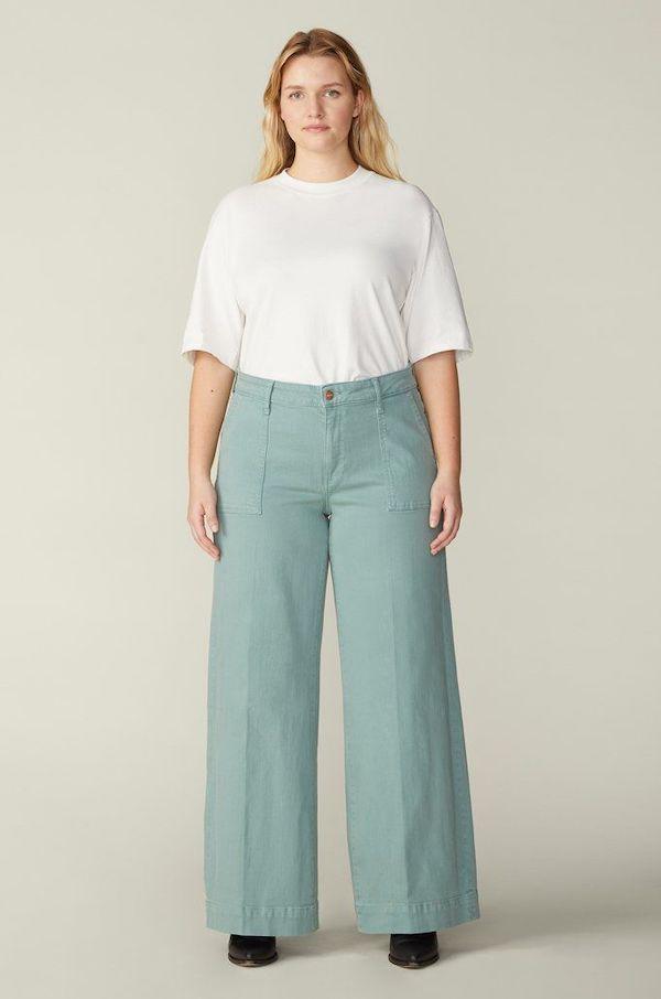 A plus-size model from Warp + Weft wearing mint green jeans.