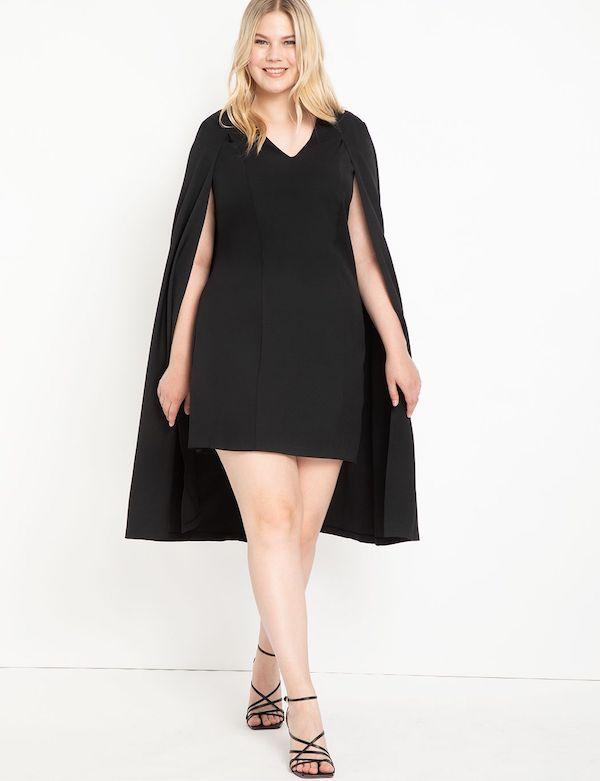 A model wearing a plus-size cape dress in black.