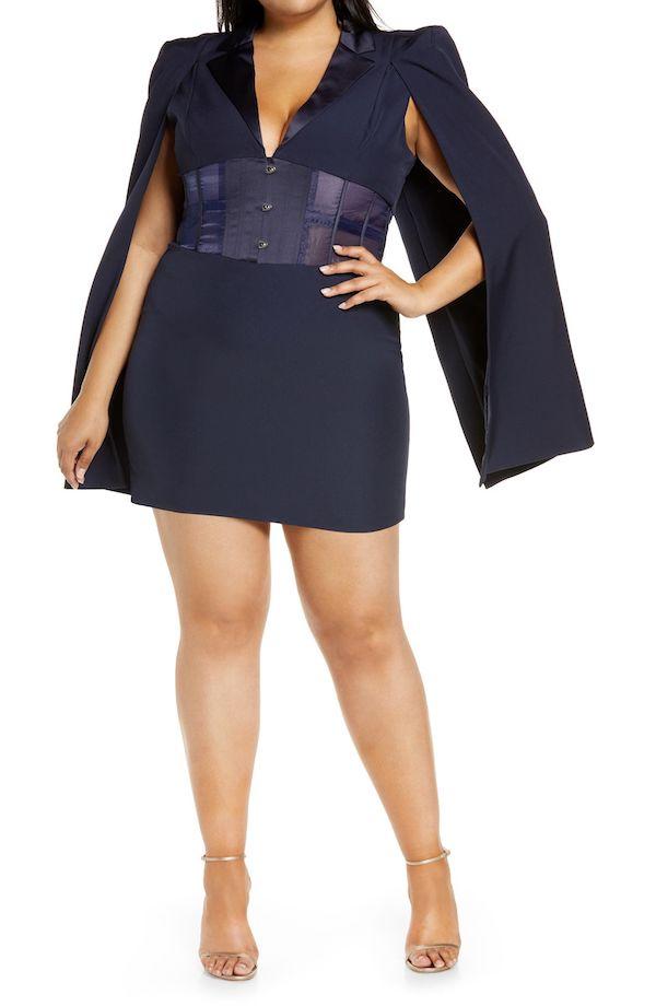 A model wearing a plus-size cape dress in navy.