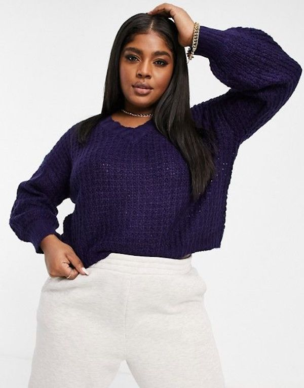 A model wearing a plus-size navy blue chenille sweater.