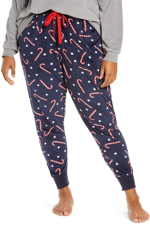 A model wearing plus-size pajama pants with candy canes.