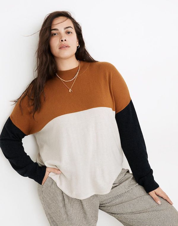 A model wearing a plus-size colorblock sweater in black, brown, and white.