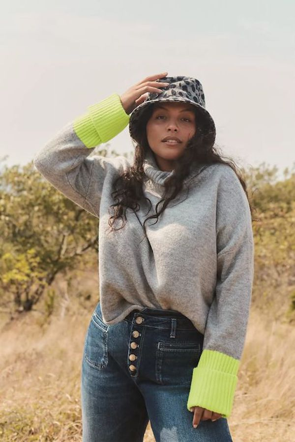 A model wearing a plus-size colorblock sweater in gray and lime green.