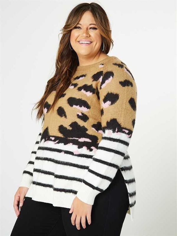 A model wearing a plus-size colorblock sweater in stripes and animal print.