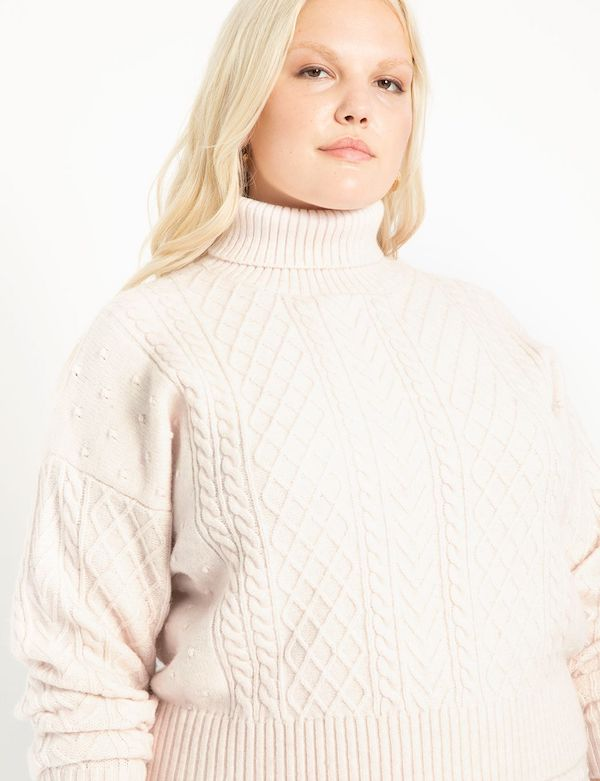 A model wearing a plus-size cropped sweater in cream.