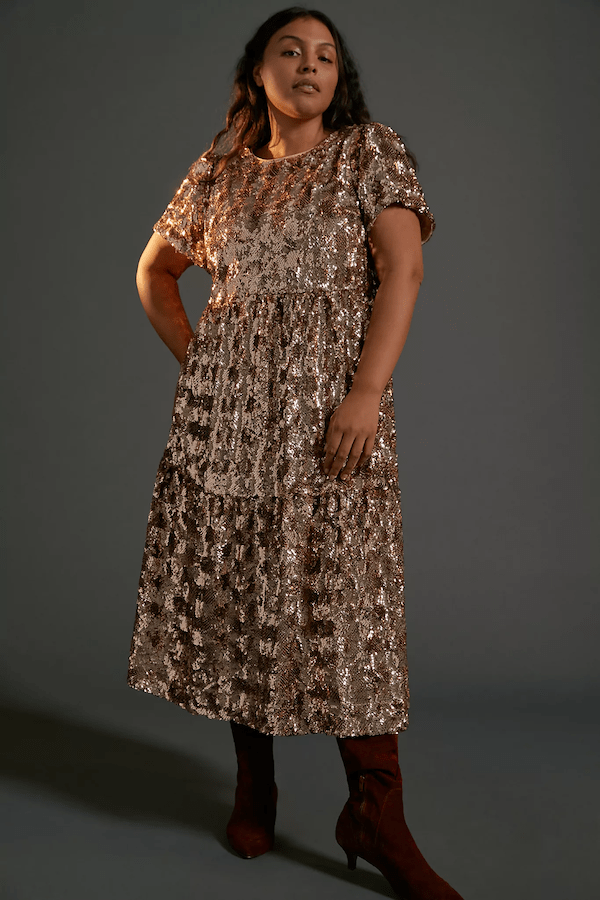 A model wearing a plus-size gold sparkly maxi dress.