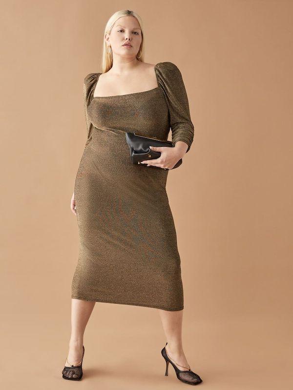 A model wearing a plus-size gold midi dress.