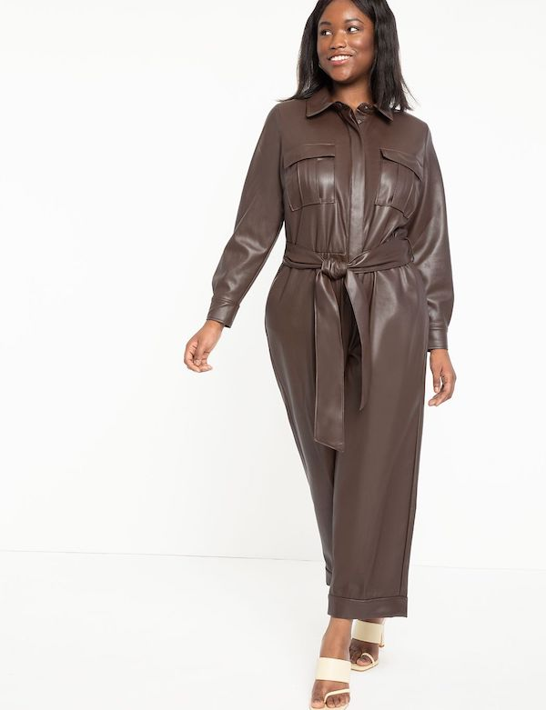 A model wearing a plus-size faux leather jumpsuit in dark brown.