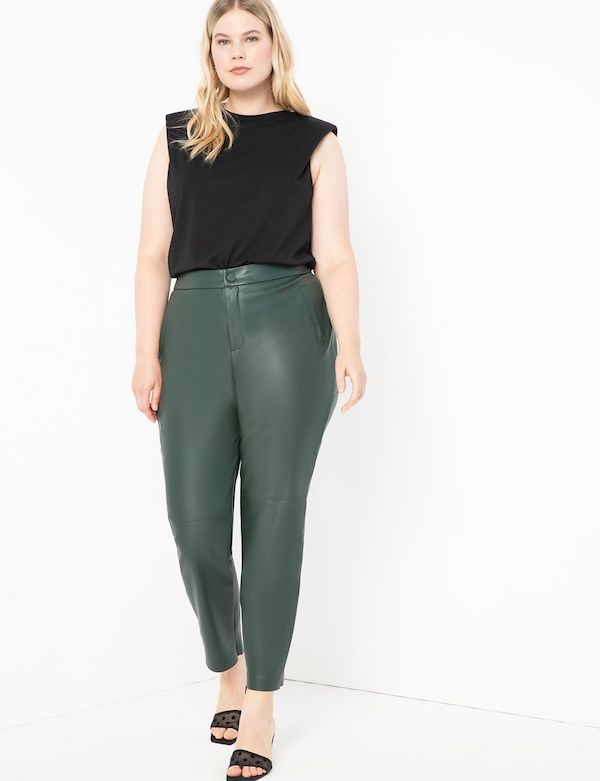 A model wearing plus-size leather pants in green.