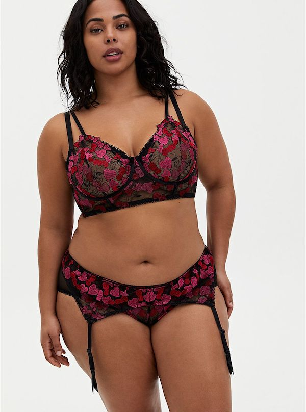 A model wearing a plus-size lingerie set in black and red floral.