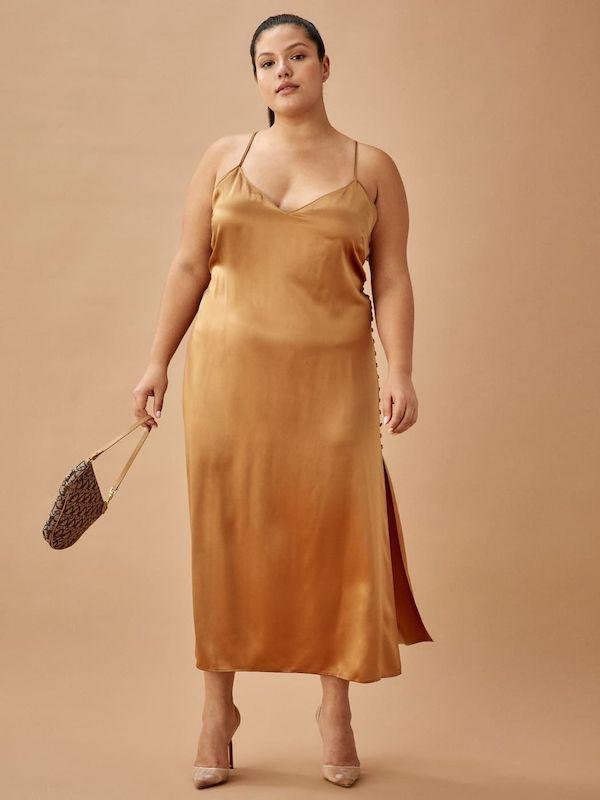 A model wearing a plus-size velvet slip dress.