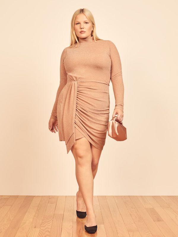 A model wearing a plus-size nude mini dress.