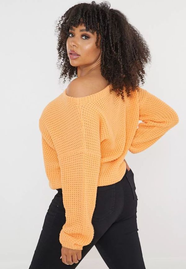 A model wearing a plus-size off-the-shoulder sweater in orangey yellow.