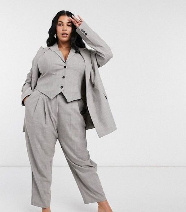 A model wearing a plus-size pant suit in gray.
