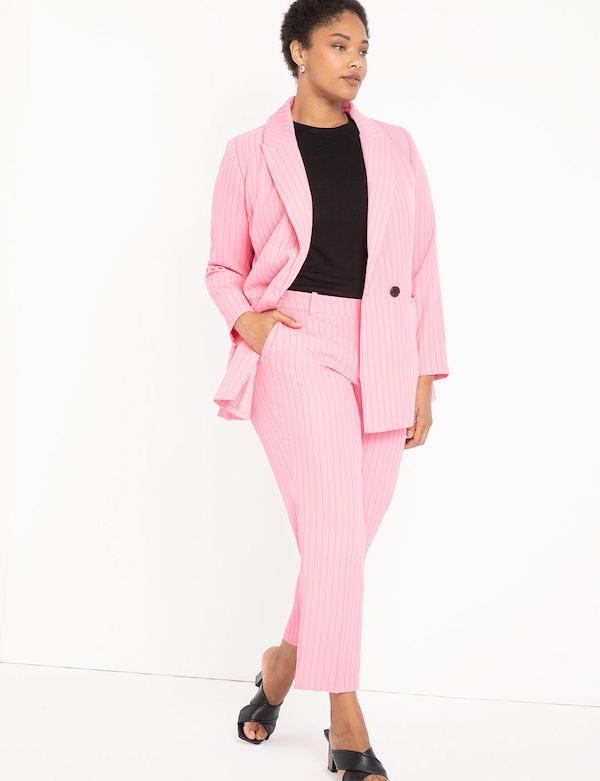 A model wearing a plus-size pant suit in light pink.