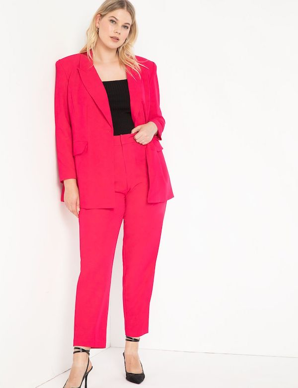 A model wearing a plus-size pant suit in hot pink.