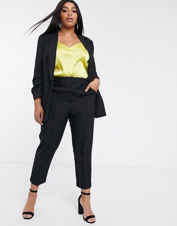 A model wearing a plus-size pant suit in black.