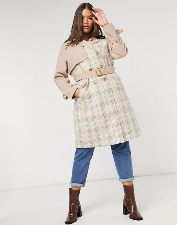 A model wearing a plus-size plaid coat in light pink and cream.