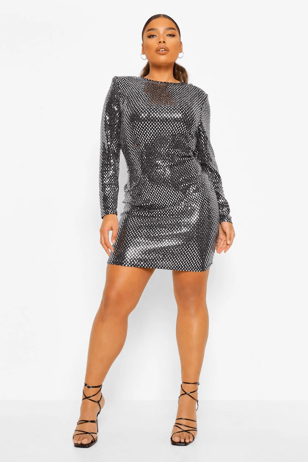 A model wearing a plus-size silver mini dress.