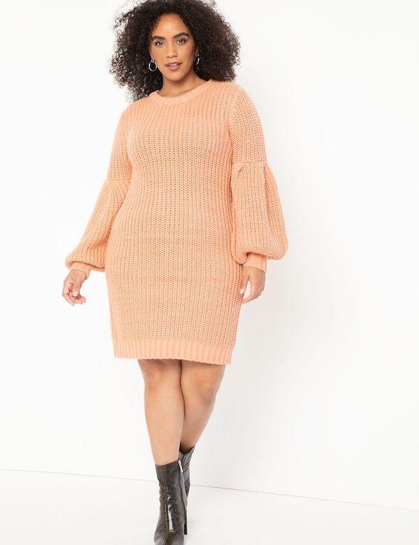 A model wearing a plus-size peach sweater dress.