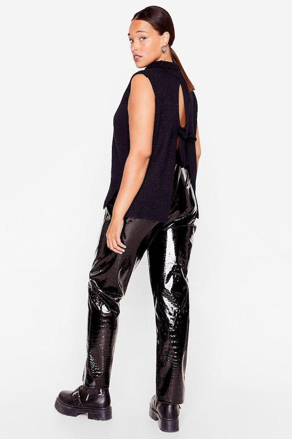 A model wearing a plus-size black sweater vest.