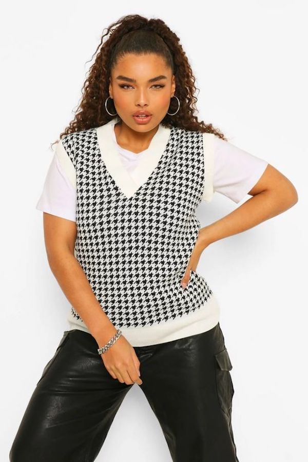 A model wearing a plus-size houndstooth sweater vest.