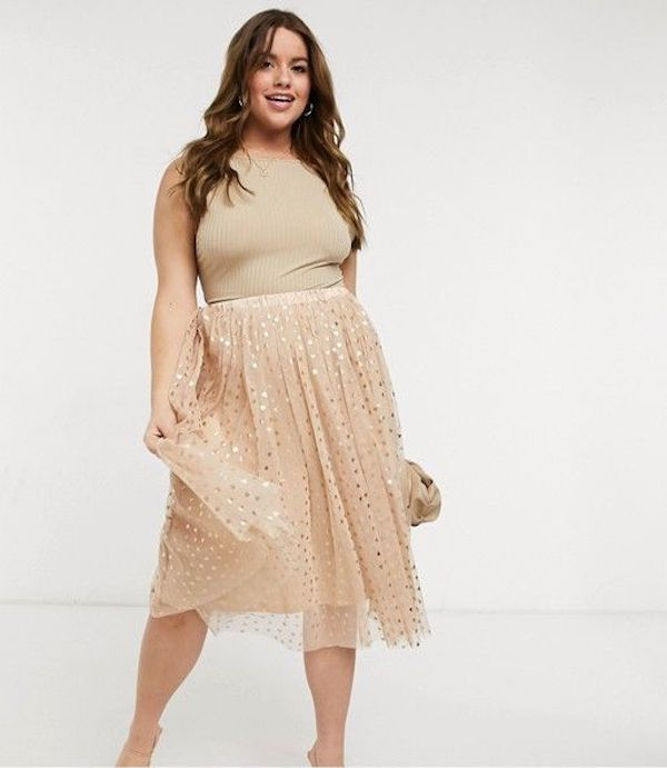 A model wearing a plus-size tan tulle skirt.
