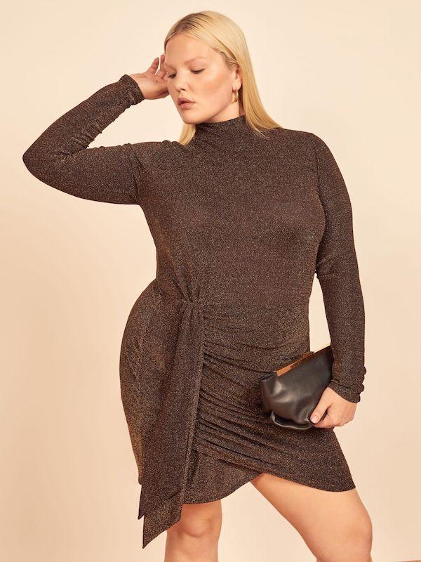 A model wearing a plus-size turtleneck dress in dark brown.