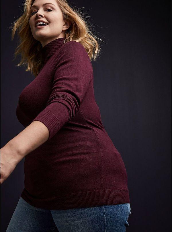 A model wearing a plus-size turtleneck sweater in dark red.