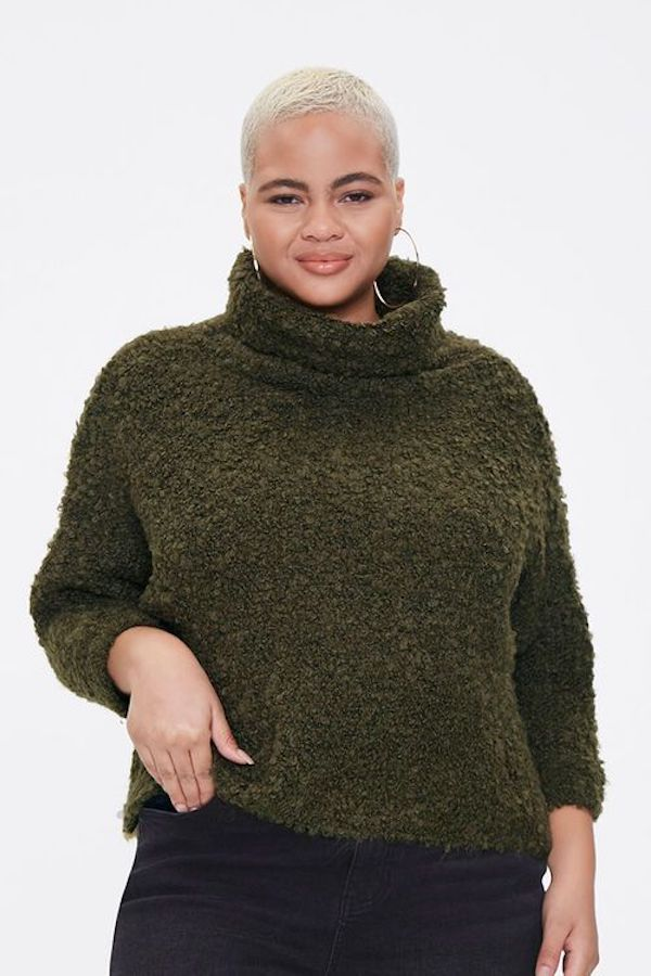 A model wearing a plus-size turtleneck sweater in dark green.