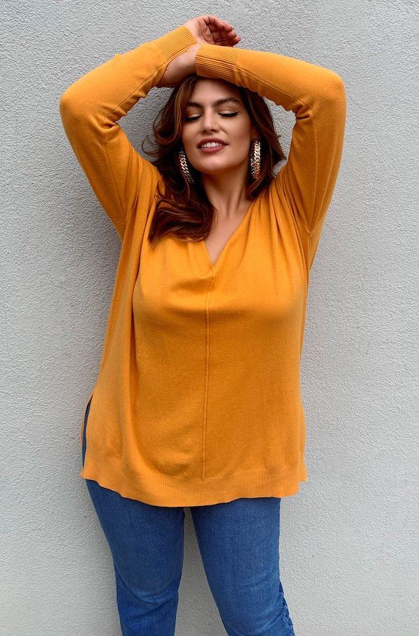 A model wearing a plus-size v-neck sweater in mustard.