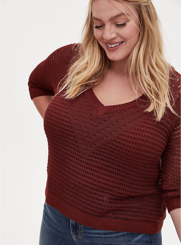 A model wearing a plus-size v-neck sweater in dark red.