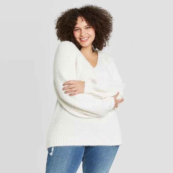 A model wearing a plus-size v-neck sweater in white.