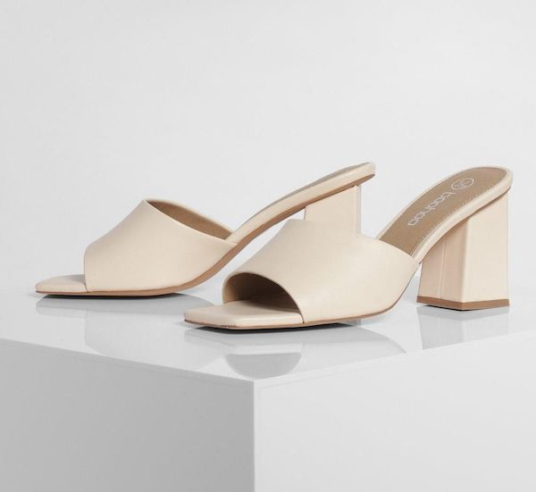 A pair of wide-fit mules in cream.