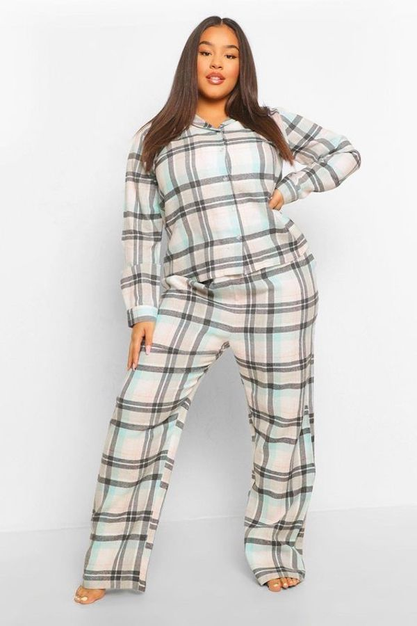 A model wearing plus-size flannel pajamas in white, black, and light blue.