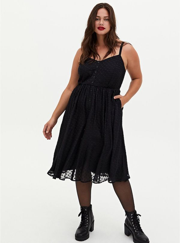 A model wearing a plus-size dress with black hearts.