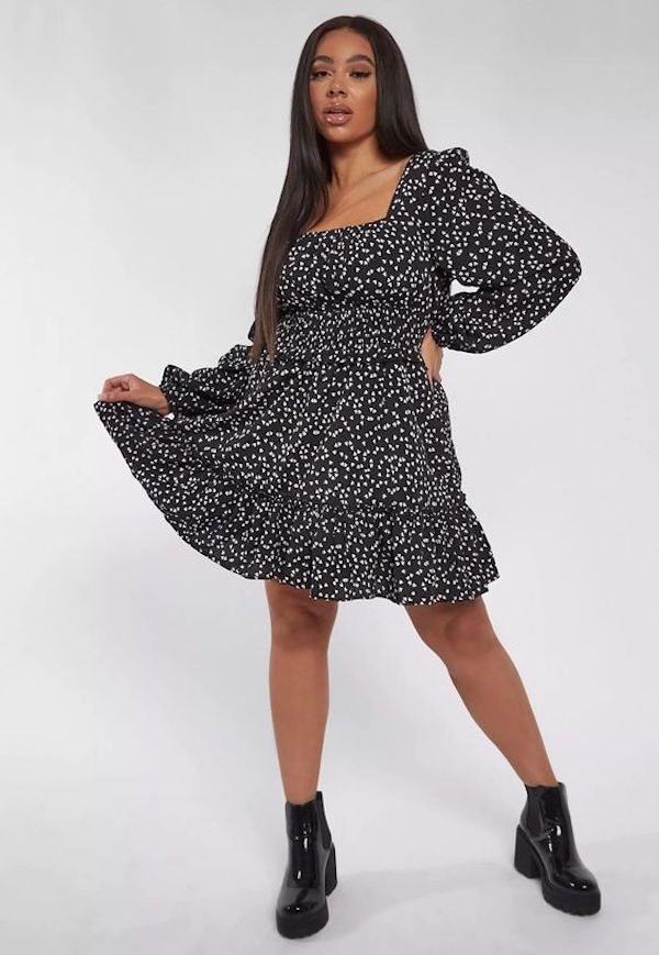A model wearing a plus-size dress in black with white hearts.