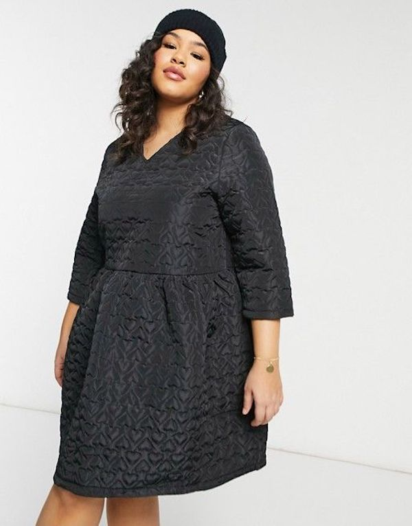A model wearing a plus-size dress in black with hearts.