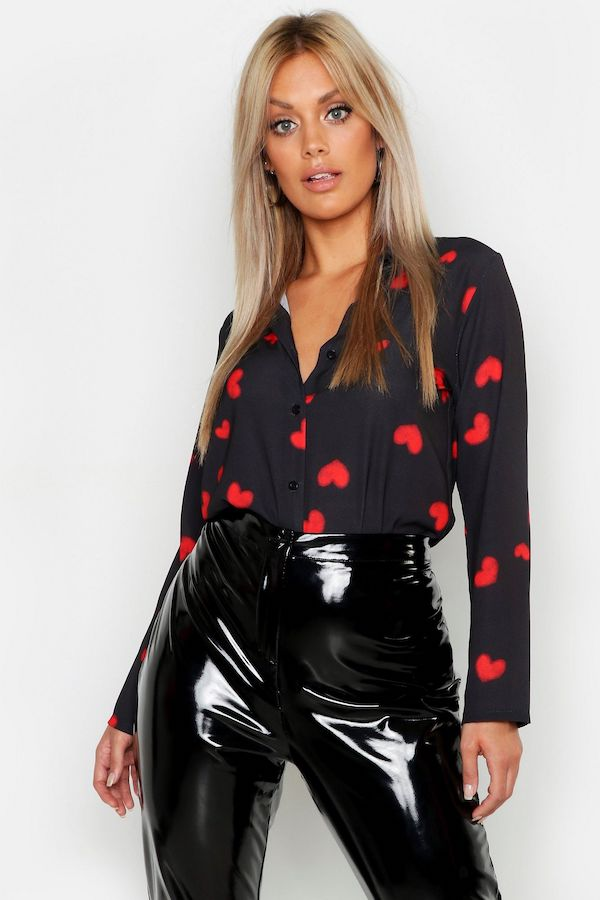 A model wearing a plus-size heart pattern top in black and red.