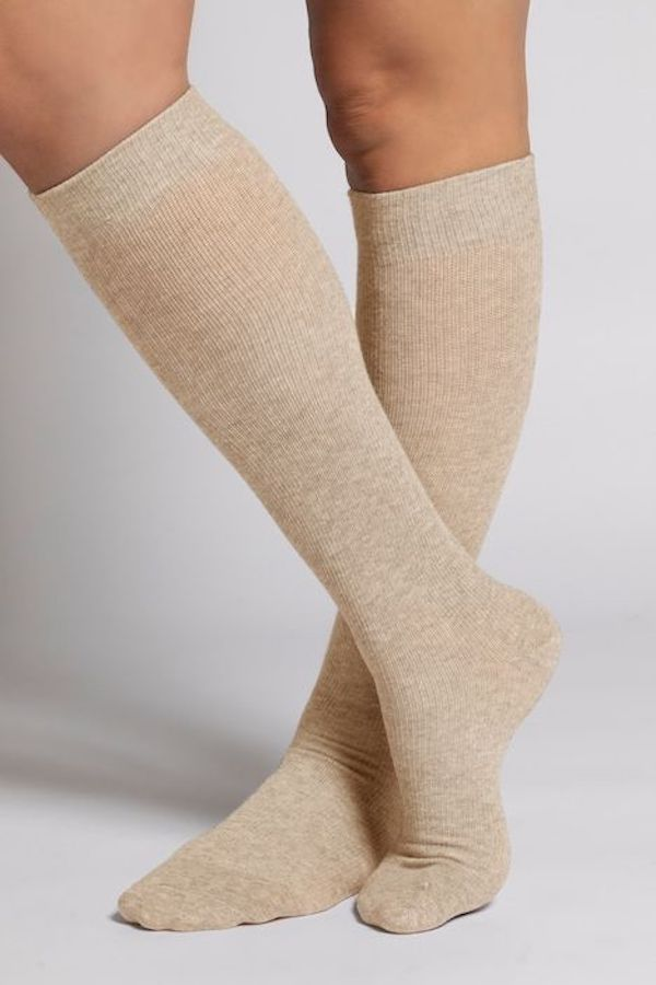 A model wearing a pair of plus-size knee-high socks in cream.