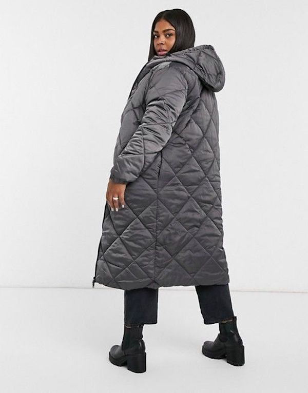 A model wearing a plus-size quilted jacket in gray.