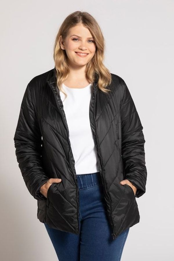 A model wearing a plus-size quilted jacket in black.